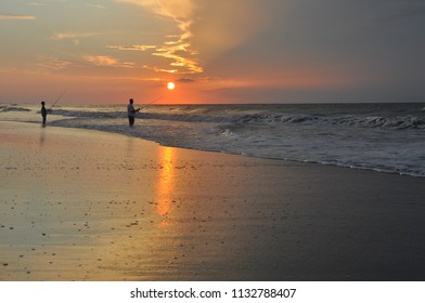 silhouette of a man and child fishing in the Atlantic Ocean at Sunrise.