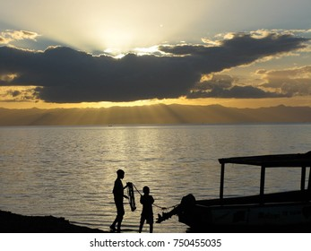 Silhouette of a man and a child tending to a boat on the shores of Lake Malawi at sunset, in Monkey Bay (also known as Lusumbwe), Malawi