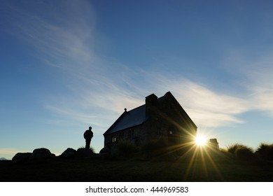 Silhouette of man and the Church of Good Shepherd at sunrise in Lake Tekapo, New Zealand