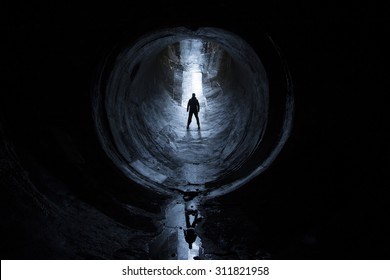 silhouette of man in circular tunnel