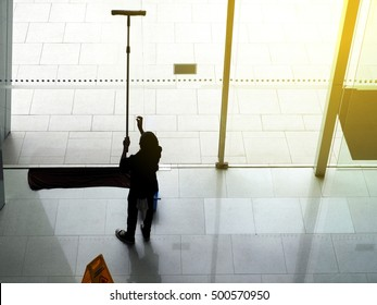 Silhouette of a man is cleaning the windows in the building