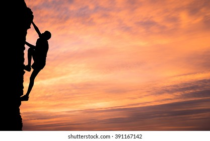 A silhouette of man climbing on stone, mountain at sunset.