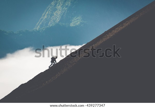 silhouette of man climbing steep mountain. Good image for adventure, struggle and success story photo.