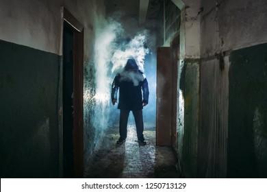 Silhouette of man in cloud of smoke standing in dark scary corridor