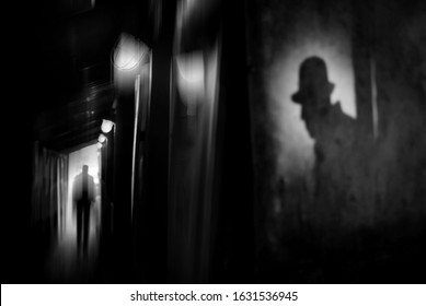 Silhouette of a man in a coat and hat in a dark alley on a rainy night. theme of violence and cruelty. blur effect