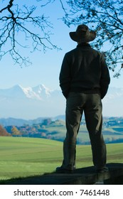 Silhouette of a man contemplating a distant chain of mountains and pastures, in Fall.