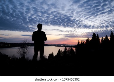 Silhouette of a man controlling a drone that is in the background with the sun setting over downtown Vancouver.