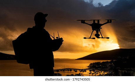 Silhouette of a man controls a drone on a sunset background