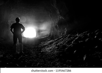 Silhouette of a man in the corridors of a creepy dark cave.