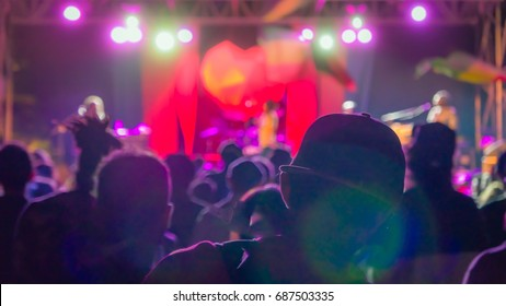 Silhouette of man in the crowd in baseball cap on reggae concert bright lights with lens flare