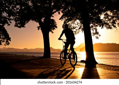 Silhouette of a Man Cycling in the Early Morning during Beautiful Warm Sunrise in Rio de Janeiro