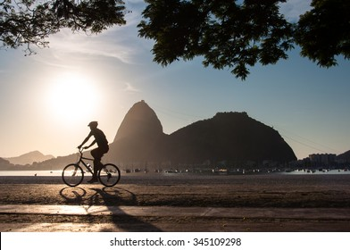 Silhouette of a Man Cycling in the Early Morning during Beautiful Warm Sunrise in Rio de Janeiro with Sugarloaf Mountain in the Horizon
