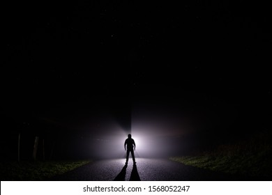 Silhouette of a man in the darkness. Night Photography. Bright light shining behind dark mysterious figure. Ghostly, mystical, surreal person standing.