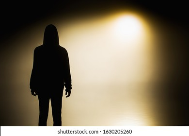 Silhouette of a man in the darkness. Night photography. Shadow in mist. Mysterious anonymous figure in darkness. Incognito person. Terrible nightmare. Ghost figure. Silhouette of man. Dark shadow.