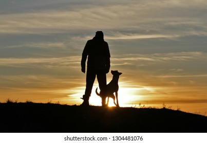 Silhouette of a man and dog Malinois against the backdrop of an incredible sunset