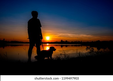 Silhouette of man and dog on sunset background.