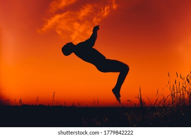 silhouette of a man doing a back flip at sunset in the summer in nature