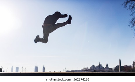 Silhouette of a man doing a jump kick in mid air