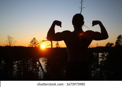 Silhouette of a man in double biceps pose. Posing in front of a beautiful sunset on a cliff.