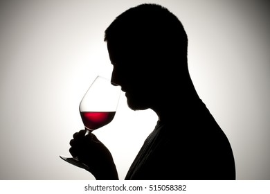 Silhouette of a man drinking and smoking.  Alcohol and substance abuse concept