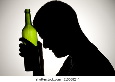 Silhouette of a man drinking wine from the bottle and smoking.  Alcohol and substance abuse concept