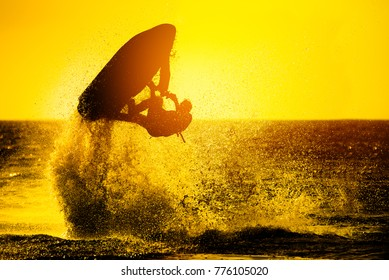 Silhouette of man drive freestyle jet ski at sunset.Professional rider do tricks in the sea.