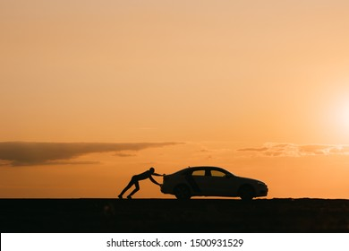 Silhouette of man driver pushing his car along on an empty road after breakdown at sunset, copy space, side view.