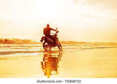 silhouette of a man driving a motorcycle on a sunset