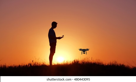 Silhouette of man with drone on sunset