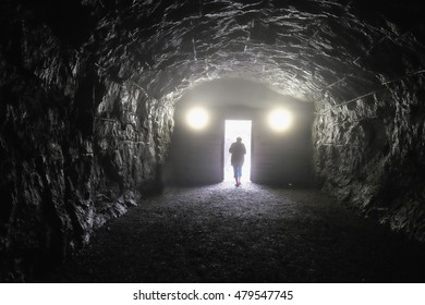 silhouette of a man at the end of the tunnel