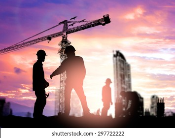 Silhouette man engineer looking construction worker under tower crane in a building site over Blurred construction worker on construction site