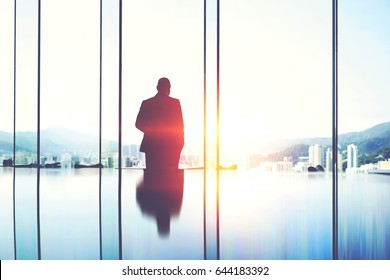 Silhouette of a man entrepreneur is pondering over the idea a business partnership which he got during a trip to China, while is standing in modern skyscraper interior against window with copy space