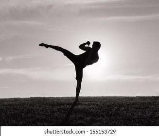 Silhouette of man exercising thai boxing
