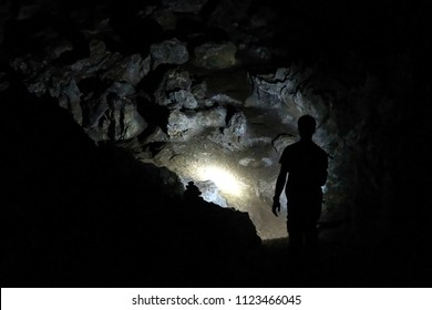 Silhouette of a man exploring a cave with a torch