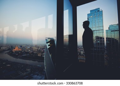 Silhouette of a man financier think about something while standing near office window background with copy space for your text message or advertising content, young male thoughtful rest after briefing