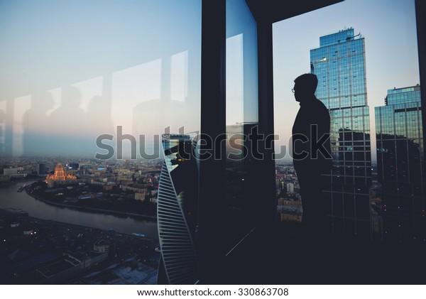 La silueta de un hombre financiero piensa en algo mientras se encuentra cerca del fondo de la ventana de la oficina con espacio para copiar tu mensaje de texto o contenido publicitario, joven hombre considerado descanso después de informar