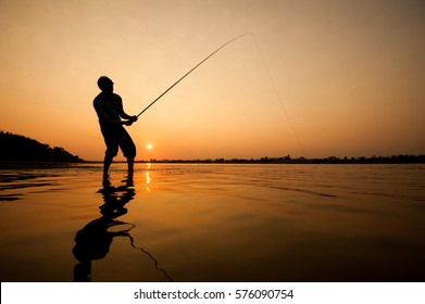 silhouette of man fishing in the river.