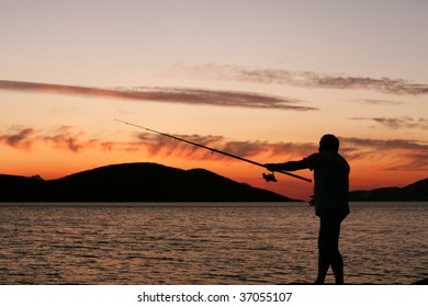 Silhouette of a man fishing in a sunset