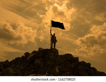 Silhouette of a man with a flag on top of a mountain, on a background of the setting sun. business, success, winner, leadership, achievement and concept of people