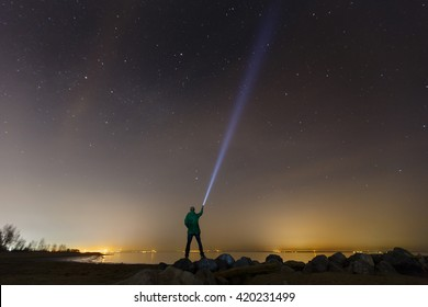 Silhouette of a man with a flashlight, observing beautiful, wide blue night sky with stars and visible Milky way galaxy. Astronomy, orientation, clear sky concept and background.