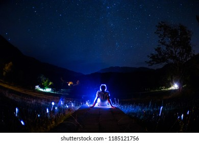 Silhouette of man in the forest on the night. Silhouette of person standing in the dark forest with light. Dark night in forest. Surreal night forest scene. Horror Halloween concept.