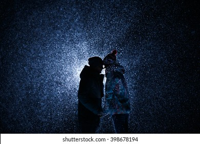 silhouette Man and girl at night under the snow. met today embrace and kiss. Suitable for sport theme, snowboards or skis. A lot of snow