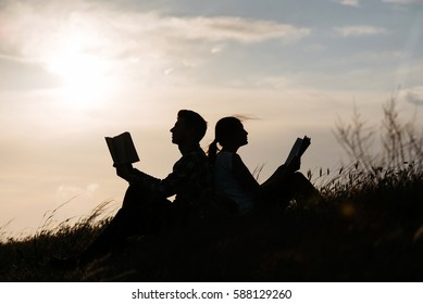 Silhouette of man and girl read book at sunset. Couple read book on grass, nature, landscape