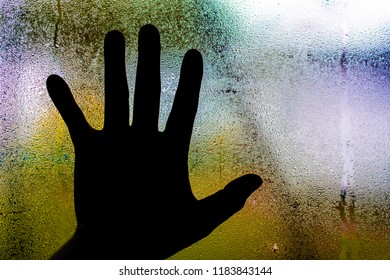 Silhouette man hand on frost glass over colorful blurred background.