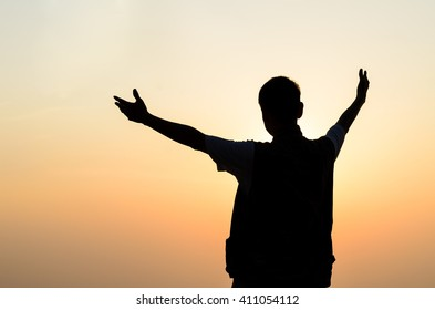 Silhouette of a man  with hands raised and sunrise sky background.