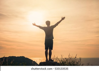 Silhouette of a man with hands raised in the sunset concept for religion, worship.Cheering man hiker open arms at sunrise mountain peak.