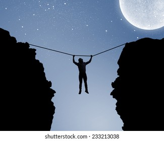 Silhouette of man hanging on rope above gap
