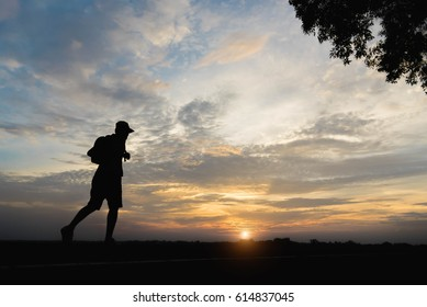 Silhouette of a man happy walking at sunset.