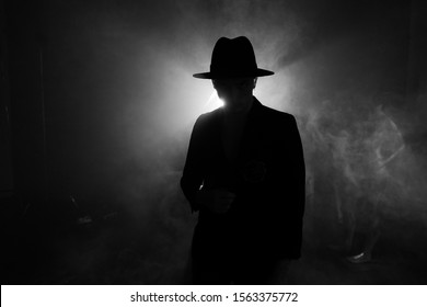 Silhouette of a man in a hat against the light, backlit guitar concert, performance with contrast
