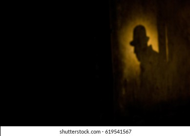 Silhouette of a man in a hat against a wall at night. Blur background with shallow depth of field bokeh effect